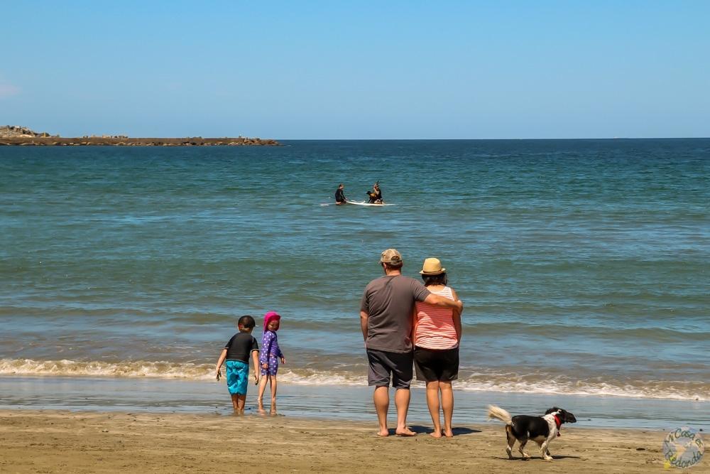 Familia viendo al perro haciendo paddle